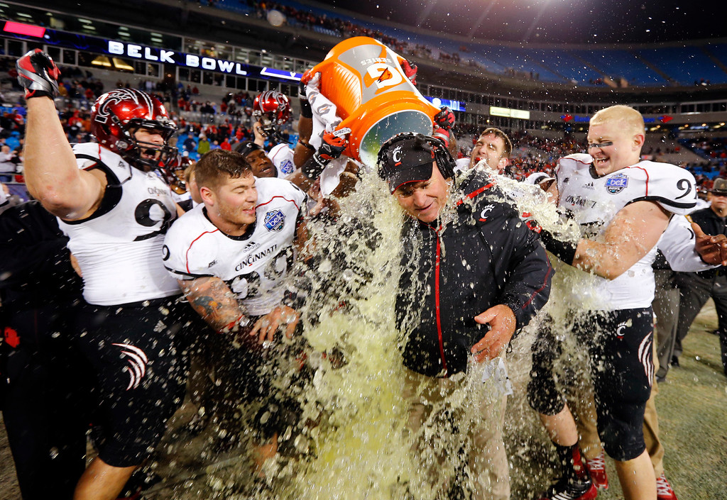 . Cincinnati head coach Steve Stripling, center, gets doused by players in the closing seconds of the Belk Bowl NCAA college football game against Duke in Charlotte, N.C., Thursday, Dec. 27, 2012. Cincinnati won 48-34. (AP Photo/Chuck Burton)