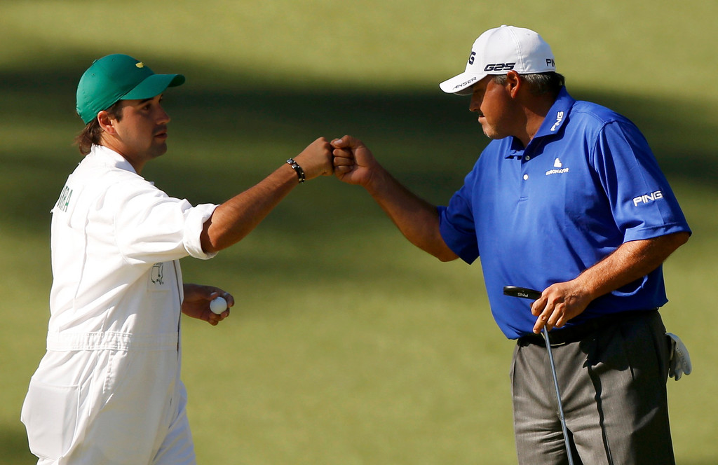 . Angel Cabrera of Argentina (R) is congratulated by his son, caddie Angel Cabrera Jr. after sinking a birdie putt on the 10th green during third round play in the 2013 Masters golf tournament at the Augusta National Golf Club in Augusta, Georgia, April 13, 2013.   REUTERS/Mike Segar