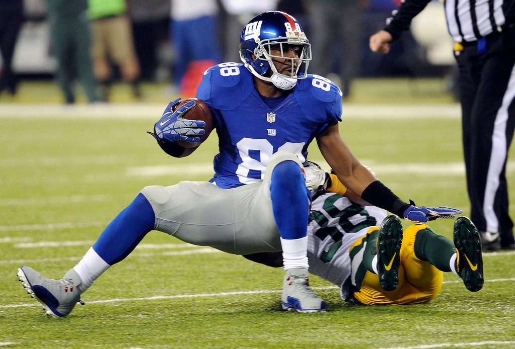 . New York Giants\' Hakeem Nicks (88) is tackled by Green Bay Packers\' Tramon Williams (38) during the first half of an NFL football game Sunday, Nov. 17, 2013, in East Rutherford, N.J. (AP Photo/Bill Kostroun)