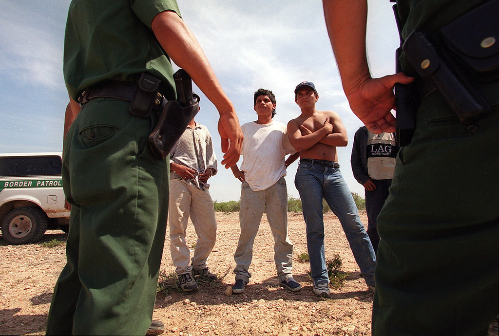 . U.S. Border Patrol agents stand watch over a group of illegal immigrants after detaining them west of Laredo, Texas May 14, 2001. Mexico and the United States on Friday announced their most sweeping effort yet to reduce the deaths of migrants, including campaigns to warn migrants of risks, a crackdown on people-smugglers and experiments with border patrol agents firing pepper gas instead of bullets. (AP Photo/John Moore)