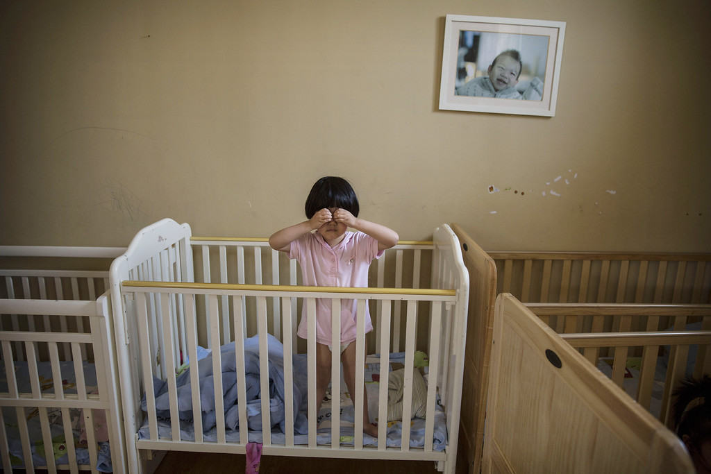 . A young orphaned Chinese girl stands in a crib at a foster care center on April 2, 2014 in Beijing, China.  (Photo by Kevin Frayer/Getty Images)