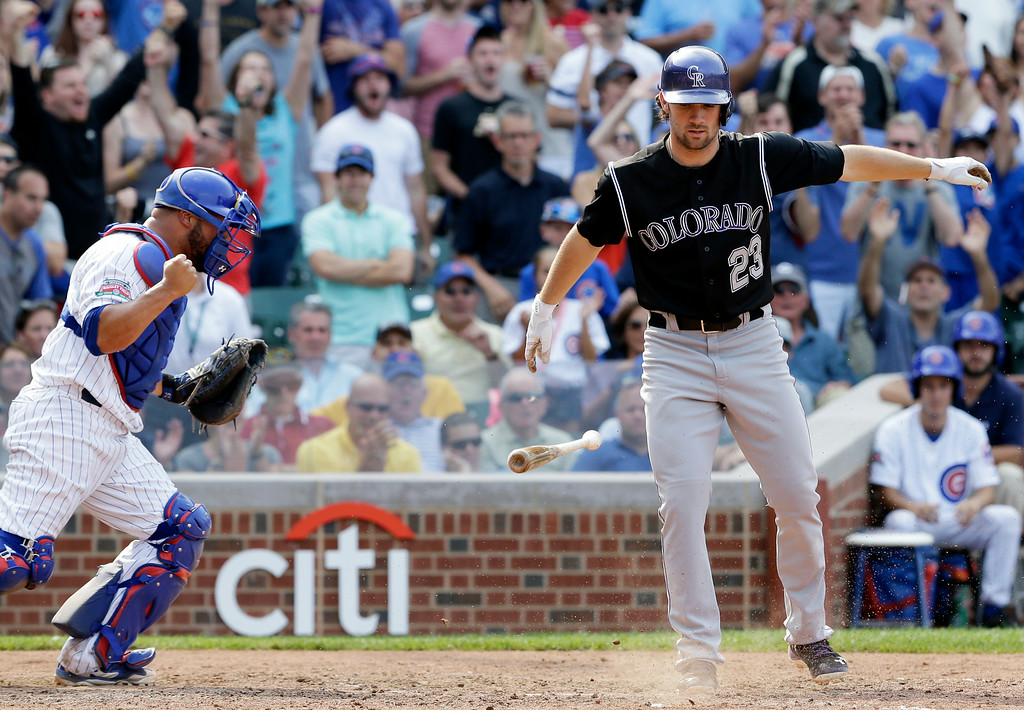 . Colorado Rockies\' Charlie Culberson, right, throws his bat after being called out on strikes as Chicago Cubs catcher Welington Castillo celebrates during the ninth inning of a baseball game in Chicago, Thursday, July 31, 2014. The Cubs won 3-1. (AP Photo/Nam Y. Huh)