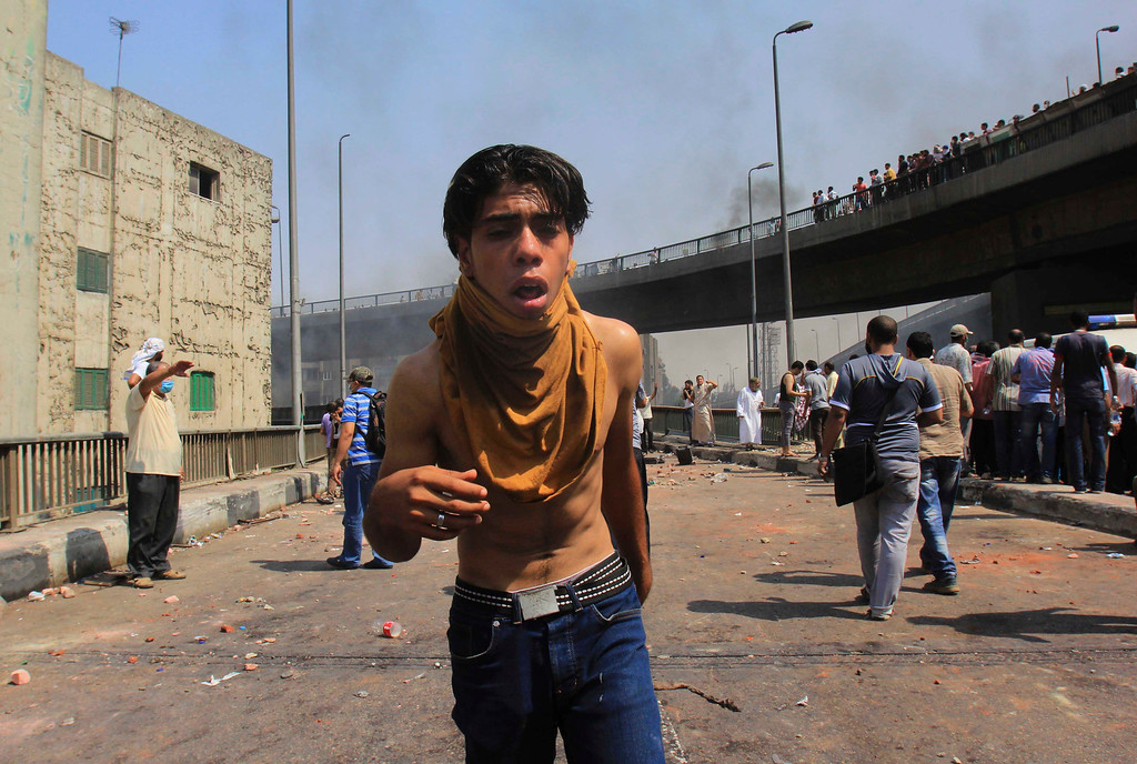 . A supporters of Egypt\'s ousted President Mohammed Morsi reacts to tear gas during clases with security forces near the largest sit-in by supporters of  Morsi in the eastern Nasr City district of Cairo, Egypt, Wednesday, Aug. 14, 2013. (AP Photo/Mohammed Abu Zeid)