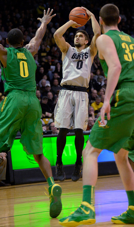 . Colorado Buffaloes guard Askia Booker (0) takes a shot over Oregon Ducks forward Mike Moser (0) during the second half January 5, 2014 at Coors Events Center. Booker had a game high of 27.  (Photo by John Leyba/The Denver Post)