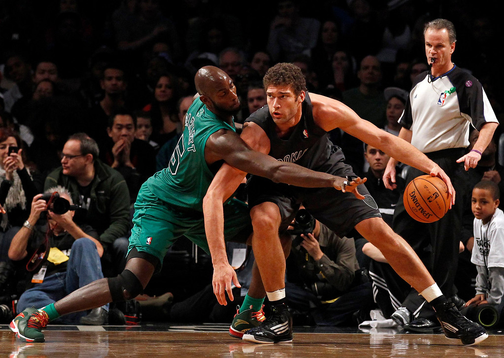 . Brooklyn Nets center Brook Lopez (R) drives to the basket defended by Boston Celtics forward Kevin Garnett in the second quarter of their NBA basketball game in New York, December 25, 2012.    REUTERS/Adam Hunger