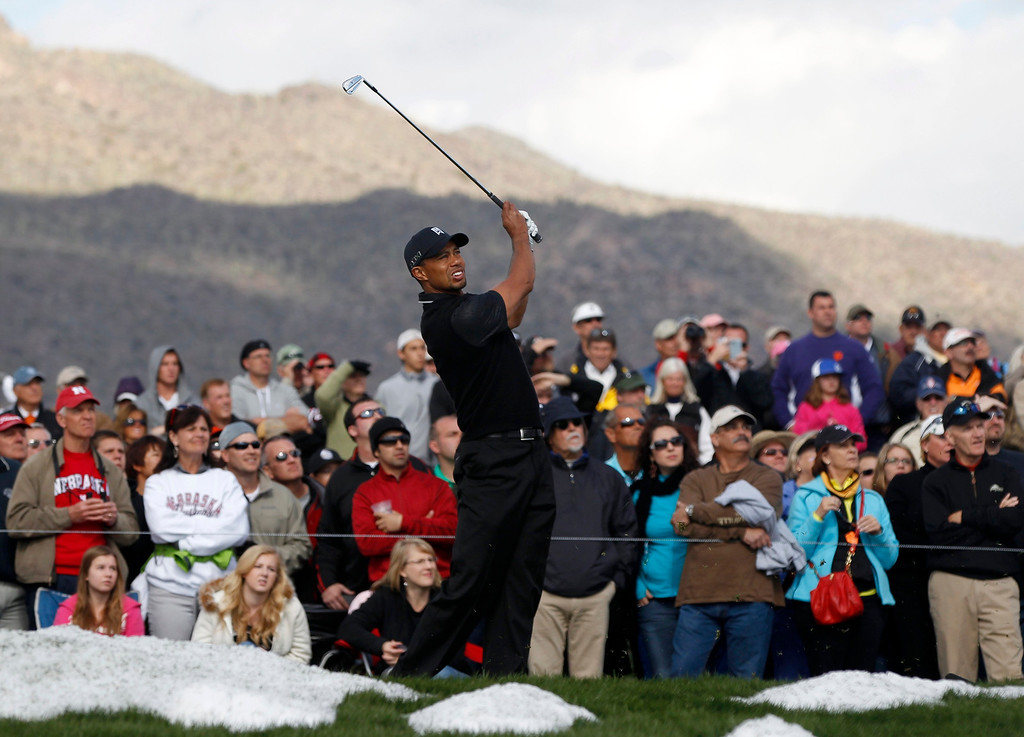 . Tiger Woods of the U.S. hits next to snow on the third tee against his compatriot Charles Howell III during their weather delayed first round of the WGC-Accenture Match Play Championship golf tournament in Marana, Arizona February 21, 2013. REUTERS/Matt Sullivan