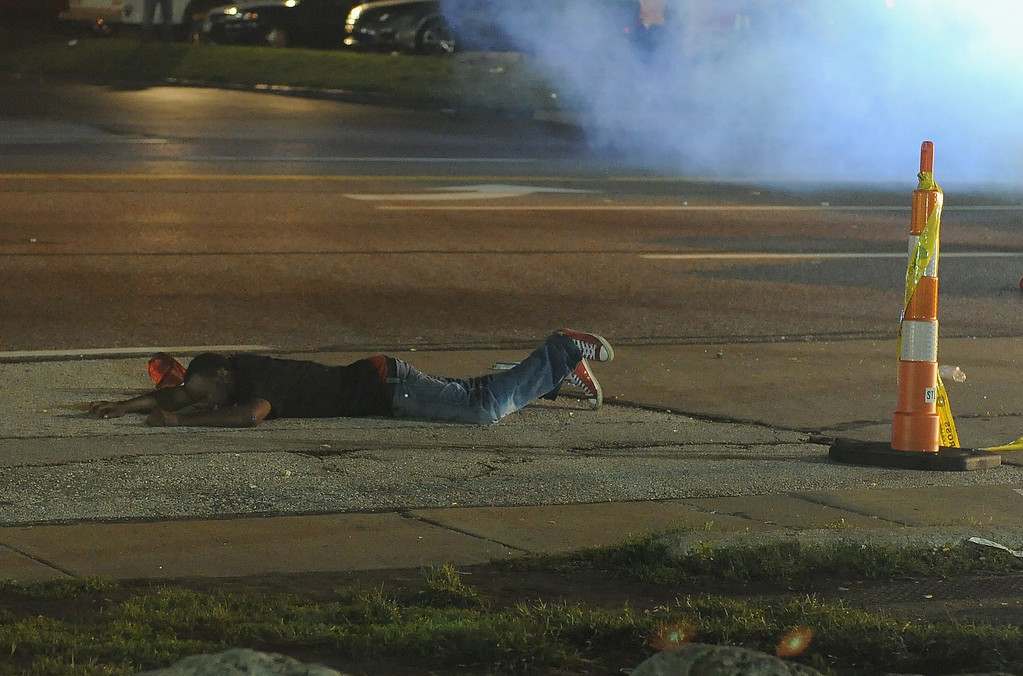 . A protestor lays in pain after being shot by a rubber bullet during a protest on West Florissant Road in Ferguson, Missouri on August 17, 2014. Riot police late Sunday hurled tear gas and marched on rioters in the St Louis suburb of Ferguson, wracked by race riots since police shot dead an unarmed black teenager.   AFP PHOTO / Michael B. Thomas/AFP/Getty Images