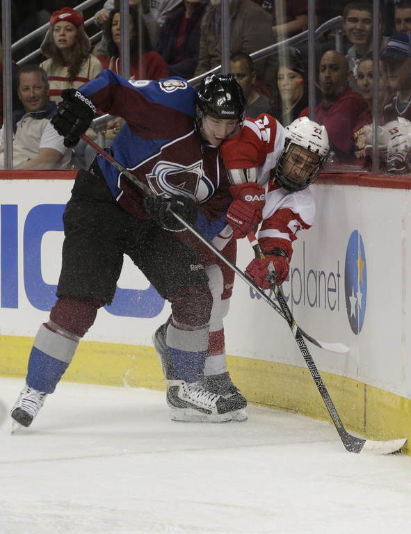 . Detroit Red Wings defenseman Kyle Quincey (27) covers the puck against Colorado Avalanche center Matt Duchene (9) in the first period of an NHL hockey game on Friday, April 5, 2013, in Denver. (AP Photo/Joe Mahoney)
