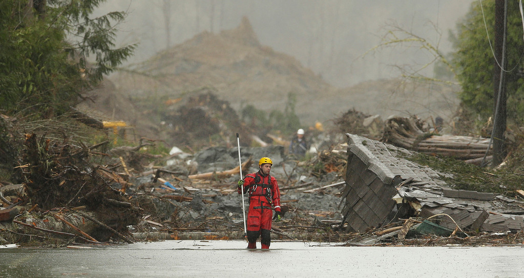. A search and rescue worker carrying a probe wades through water covering Washington Highway 530 Thursday, March 27, 2014, on the eastern edge of the massive mudslide that struck Saturday near Darrington, Wash. as heavy equipment moves trees and other debris in the background. (AP Photo/Ted S. Warren, Pool)