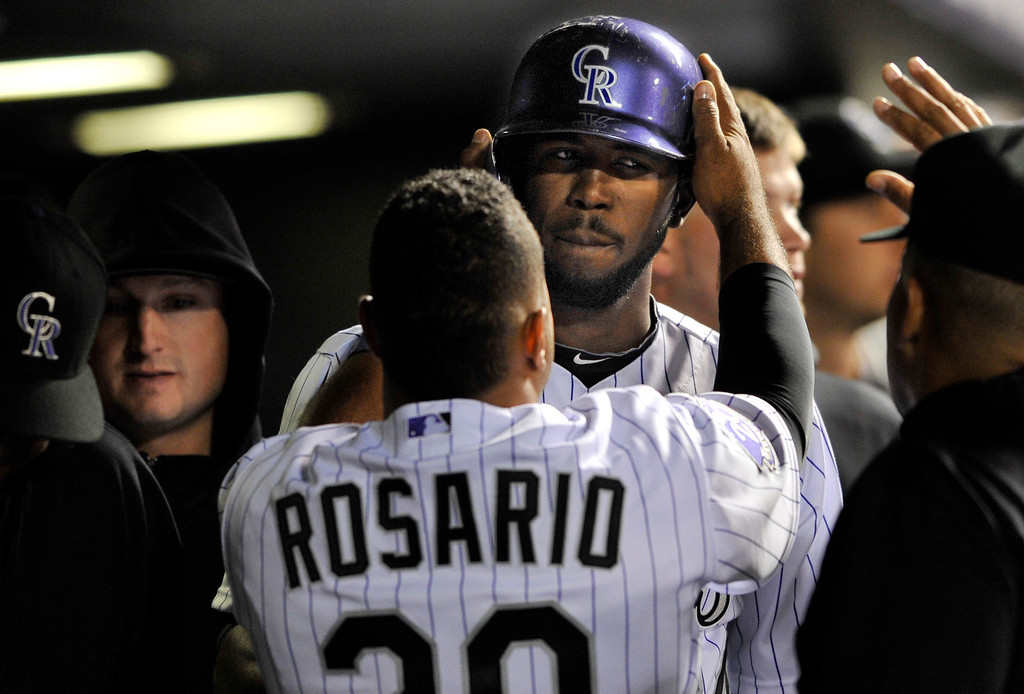 . Colorado Rockies\' Dexter Fowler, top, is congratulated by teammate Wilin Rosario (20) after scoring against the San Diego Padres during the fifth inning of a baseball game on Saturday, April 6, 2013, in Denver. (AP Photo/Jack Dempsey)