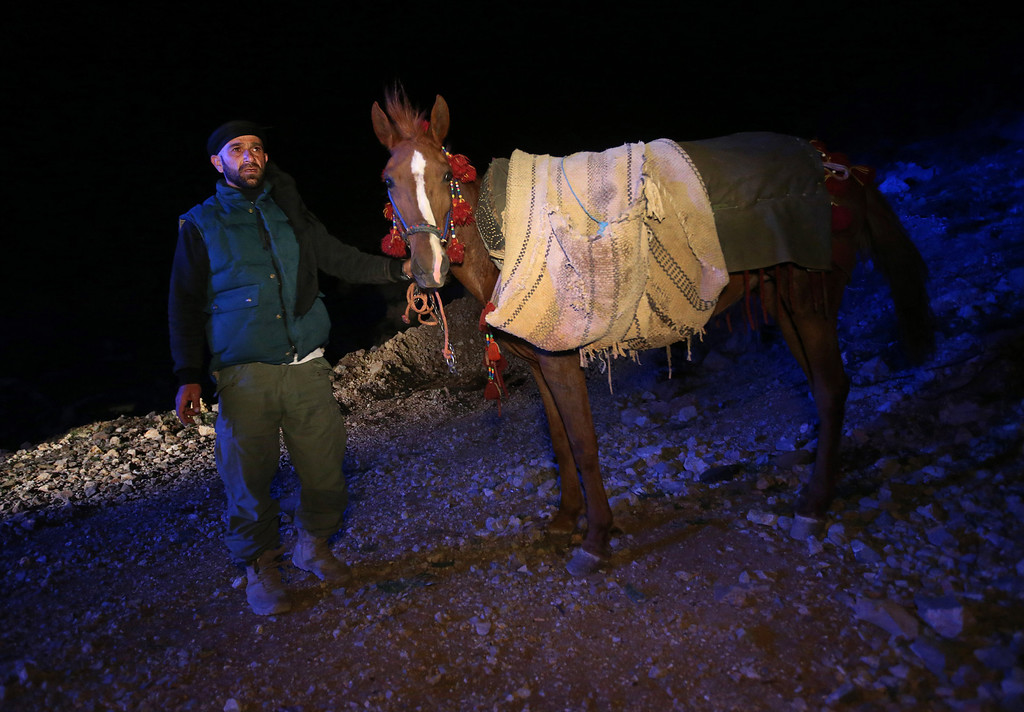 . In this picture taken early Sunday, April 20, 2014, Ibrahim Abdulghani, 32, leads his horse loaded with the belongings of Syrian refugees as he descends from the 2,814-meter (9,232-foot) high Mount Hermon (Jabal el-Sheikh), in southeast Lebanon. Abdulghani, from Syria, works as a construction worker during the day in Lebanon and volunteers at night to help Syrians escape.  Only the most desperate risk the perilous journey, Abdulghani said. The list of dangers, he said, runs long: crossfire from clashes; snipers; airstrikes; snow in winter and pouring rain in spring. For fear of being spotted by snipers while climbing up the mountain on the Syrian side, smoking is prohibited. �They can light up a cigarette when they descend into Lebanon,� he said.(AP Photo/Hussein Malla)