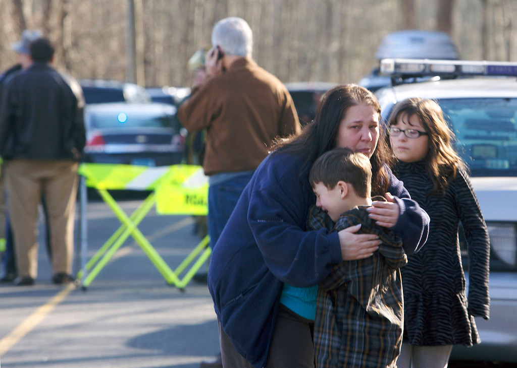. A young boy is comforted outside Sandy Hook Elementary School after a shooting in Newtown, Connecticut, December 14, 2012. A shooter opened fire at the elementary school in Newtown, Connecticut, on Friday, killing several people including children, the Hartford Courant newspaper reported. REUTERS/Michelle McLoughlin