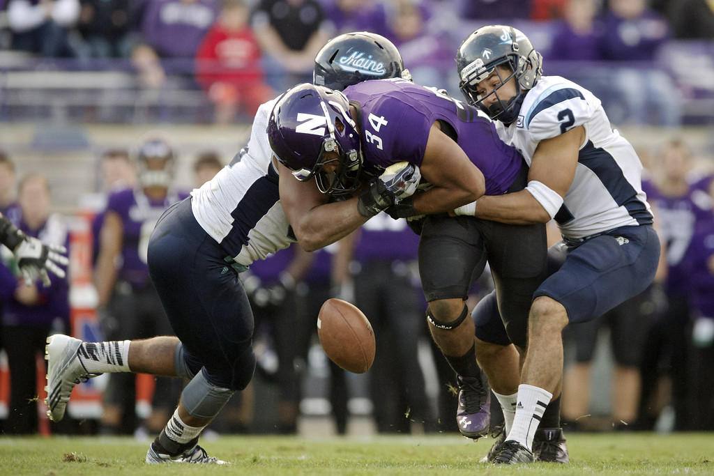 . EVANSTON, IL - SEPTEMBER 21:  Warren Long #34 of the Northwestern Wildcats funnels the ball as he\'s tackled by Trevor Bates #92 and Cabrinni Goncalves #2 of the Maine Black Bears during the fourth quarter of their college football game at Ryan Field on September 21, 2013 in Evanston, Illinois. (Photo by John Gress/Getty Images)