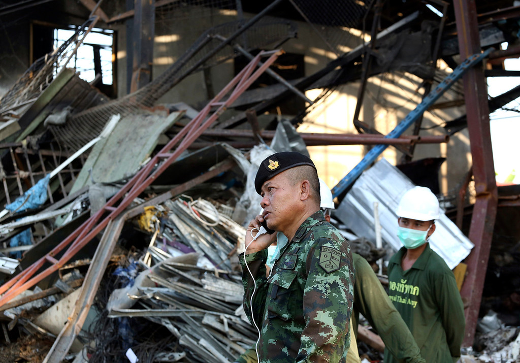 . A Thai soldier talks on a mobile phone as his colleague, right, stands nearby while working at an explosion site at a scrap shop in Bangkok, Thailand Wednesday, April 2, 2014. (AP Photo/Apichart Weerawong)
