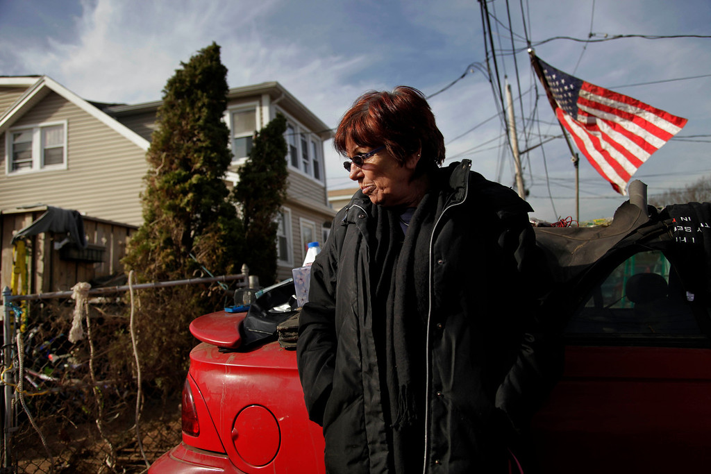 ". FILE - In this Nov. 20, 2012 file photo, Marge Gatti stands in front of her home, which was damaged by Superstorm Sandy, in the Midland Beach section of the Staten Island borough of New York. Six months after the storm, Gatti, the matriarch of her family, said ""The whole family\'s separated, and it\'s terrible, you know?\"" The flood-soaked place was demolished months ago, and they\'re waiting for a government buyout. Now the family is scattered across New Jersey, New York and Texas.   (AP Photo/Seth Wenig, File)"
