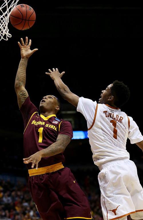 . Jahii Carson #1 of the Arizona State Sun Devils shoots against Isaiah Taylor #1 of the Texas Longhorns in the first half during the second round of the 2014 NCAA Men\'s Basketball Tournament at BMO Harris Bradley Center on March 20, 2014 in Milwaukee, Wisconsin.  (Photo by Jonathan Daniel/Getty Images)