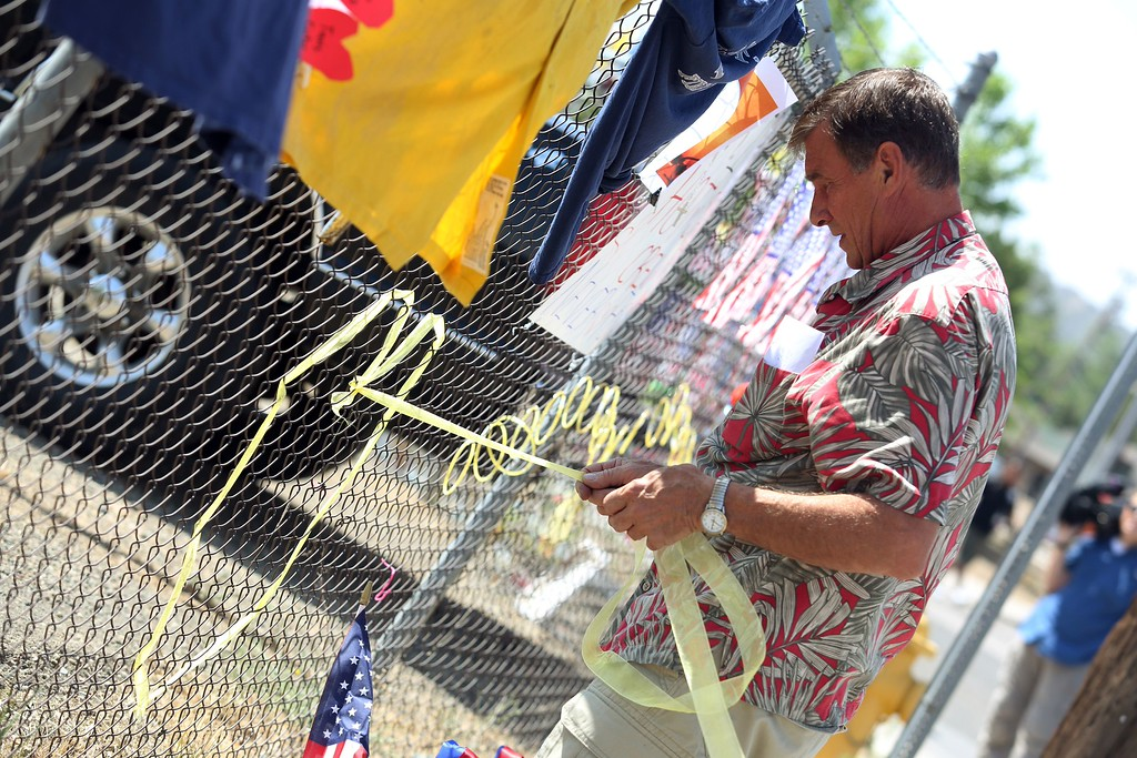 . In honor of the 19 fallen firefighters, Prescott resident Dave Anderson ties a yellow ribbon in a heart shape on a fence outside of Granite Mountain Hotshots Fire Station 7 in Prescott, Arizona July 2, 2013. AFP PHOTO / KRISTA  Kennell/AFP/Getty Images