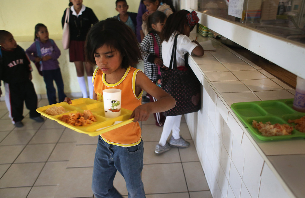 . NOGALES, MEXICO - MARCH 05:  Children receive a free lunch at the Home of Hope and Peace kitchen on March 5, 2013 in Nogales, Mexico. The non-profit organization feeds some 100 children each school day, many of whom\'s parents work at the nearby Tirabichi garbage dump, picking out recyclables for a living. Some of them were undocumented workers who were deported from the United States to Mexico.  (Photo by John Moore/Getty Images)