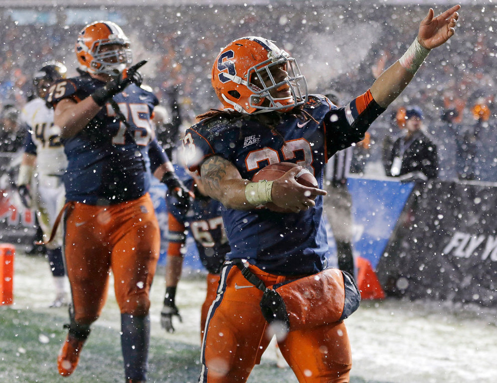 . Syracuse running back Prince-Tyson Gulley (23) and guard Zack Chibane (75) celebrate Gulley\'s third-quarter touchdown against West Virginia in the Pinstripe Bowl NCAA college football game at Yankee Stadium in New York, Saturday, Dec. 29, 2012. Syracuse won 38-14. (AP Photo/Kathy Willens)