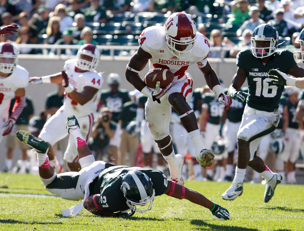. Indiana cornerback Tim Bennett (24) hurdles Michigan State receiver Andre Sims Jr. (21) while returning an interception during the fourth quarter of an NCAA college football game, Saturday, Oct. 12, 2013, in East Lansing, Mich. Michigan State won 42-28. (AP Photo/Al Goldis)