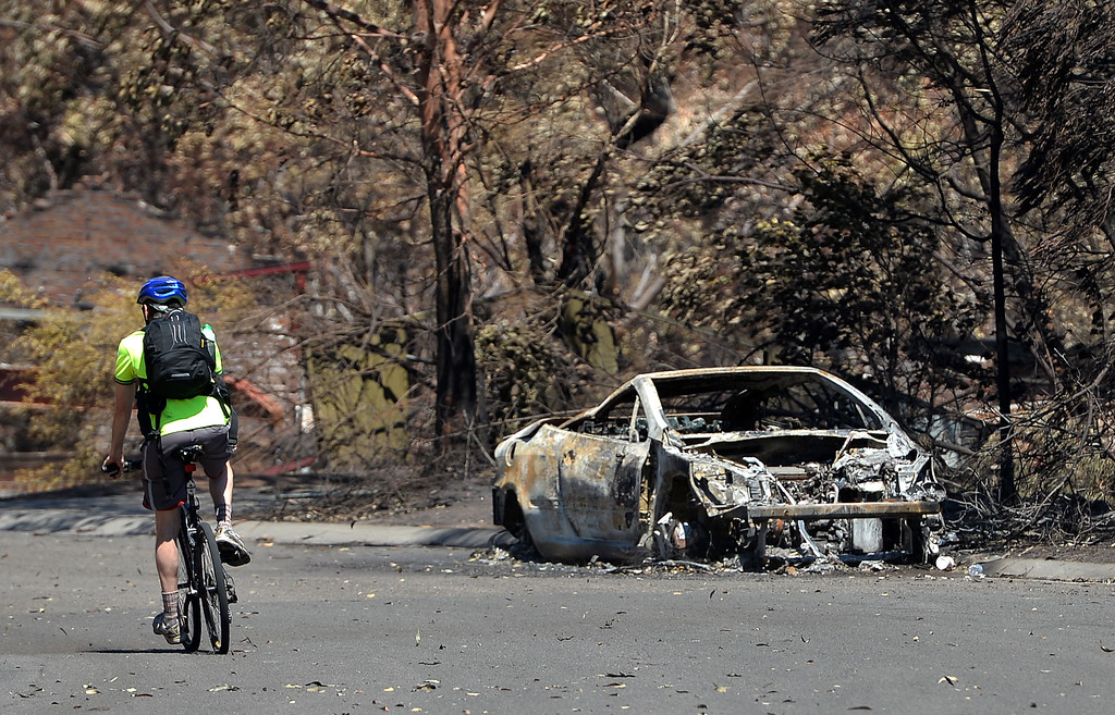 . A man rides past a car burnt out by recent bush fires in Springwood in the Blue Mountains on October 23, 2013.  Firefighters in Australia battled hot, dry winds and soaring temperatures as new blazes began breaking out in a week-long bushfire disaster that shows no signs of easing. AFP PHOTO / Saeed  KHAN/AFP/Getty Images
