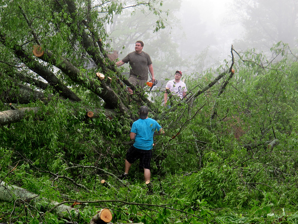 . Friends and neighbors work to cut down large trees that fell near homes during a tornado in the heavily damaged Joyner neighborhood on Tuesday, April 29, 2014 in Tupelo. Miss.   (AP Photo/Adrian Sainz).