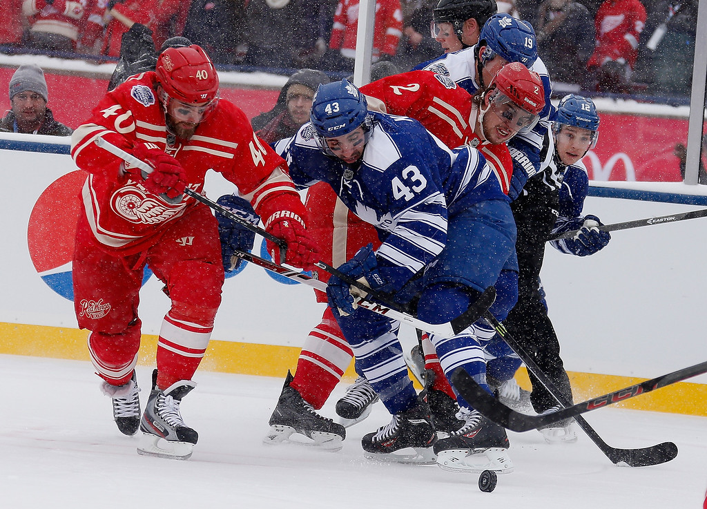 . Henrik Zetterberg #40 of the Detroit Red Wings and Nazem Kadri #43 of the Toronto Maple Leafs fight for the puck during the first period of the 2014 Bridgestone NHL Winter Classic at Michigan Stadium on January 1, 2014 in Ann Arbor, Michigan. (Photo by Gregory Shamus/Getty Images)