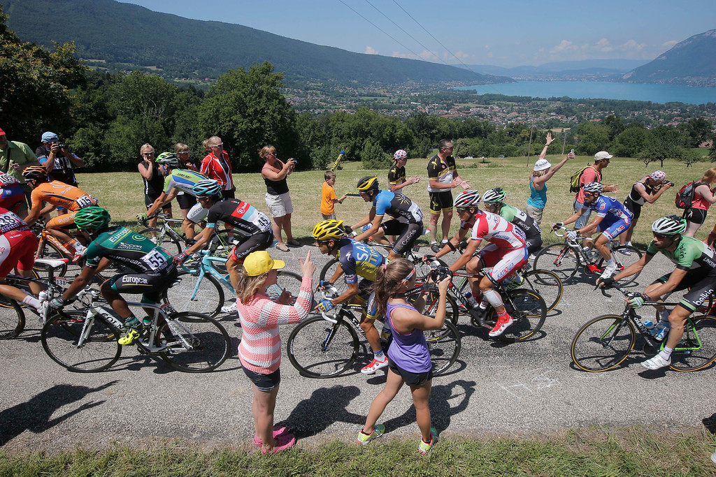 . The pack with Spain\'s Alberto Contador, center, passes Annecy lake, background, during the 20th stage of the Tour de France cycling race over 125 kilometers (78.1 miles) with start in in Annecy and finish in Annecy-Semnoz, France, Saturday July 20 2013. (AP Photo/Laurent Cipriani)