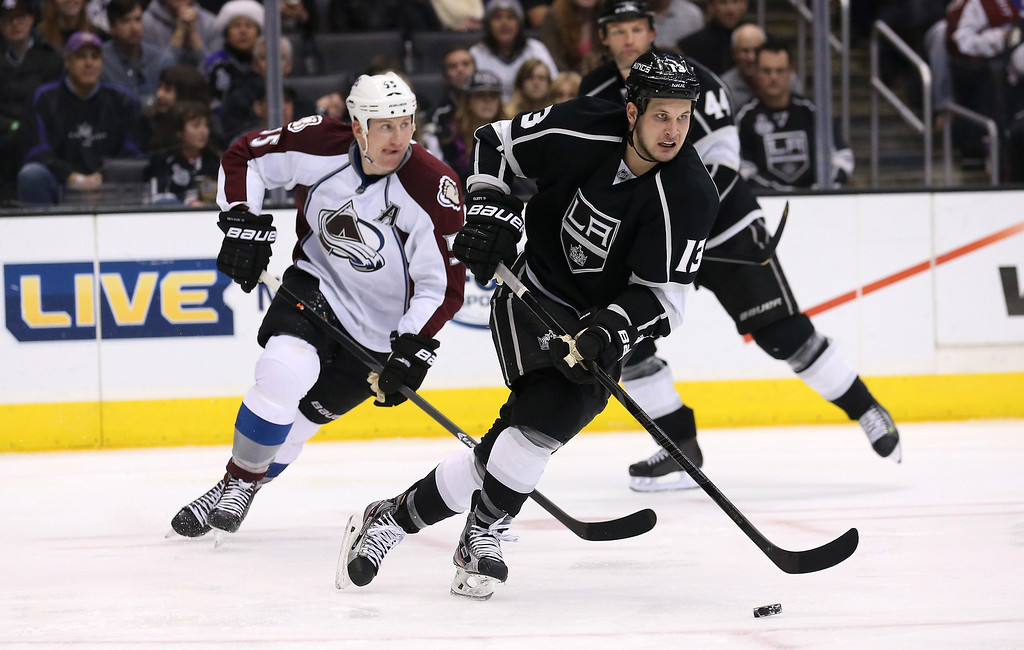 . LOS ANGELES, CA - DECEMBER 21:  Kyle Cifford #13 of the Los Angeles Kings carries the puck away from Cody McLeod #55 of the Colorado Avalanche at Staples Center on December 21, 2013 in Los Angeles, California.  The Kings won 3-2 on a shootout.  (Photo by Stephen Dunn/Getty Images)