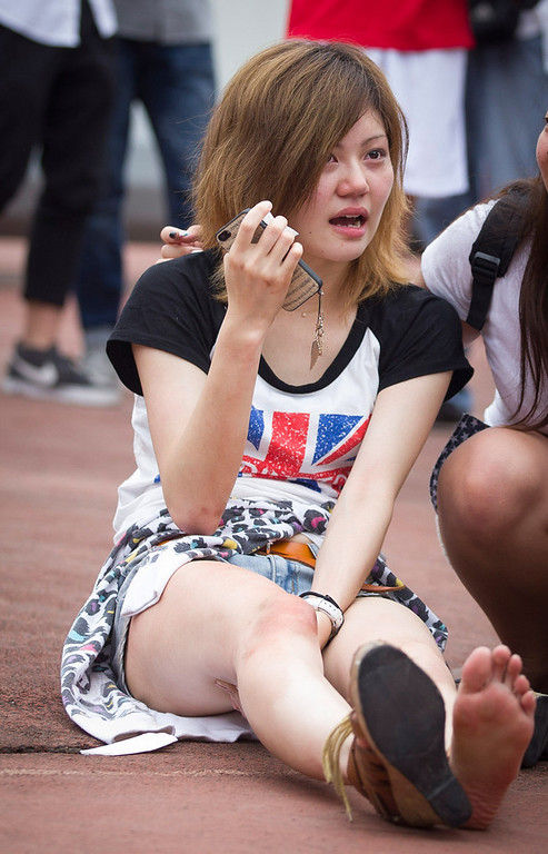 . A young woman cries after being caught and hurt in a crush of people as David Beckham arrived at Tongji University on June 20, 2013 in Shanghai, China. The stampede is reported to have left five people injured and hospitalised. (Photo by Getty Images)