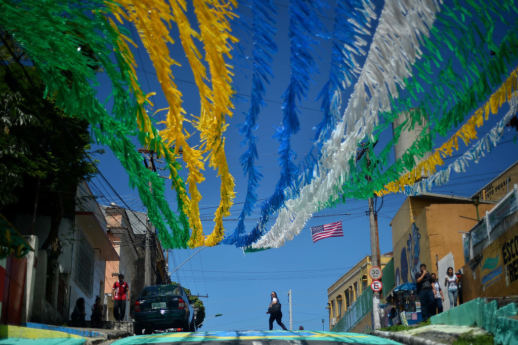 . A woman crosses a road under street decorations in Manaus, one of the host cities of the 2014 FIFA World Cup, on June 13, 2014, on the eve of a game between England and Italy. BEN STANSALL/AFP/Getty Images
