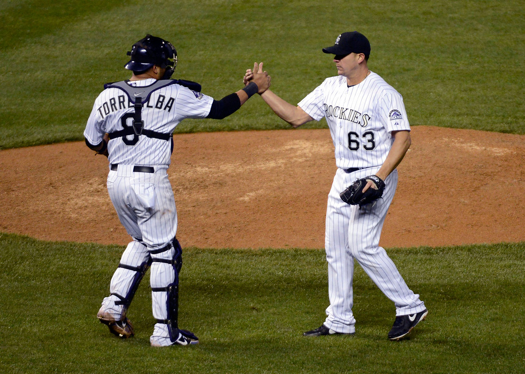 . DENVER, CO. - MAY 07: Yorvit Torrealba (8) of the Colorado Rockies shakes hands with Rafael Betancourt (63) of the Colorado Rockies recording his save in the ninth inning against the New York Yankees May 7, 2013 at Coors Field. The Colorado Rockies defeated the New York Yankees 2-0 in the first of a three game set. (Photo By John Leyba/The Denver Post)