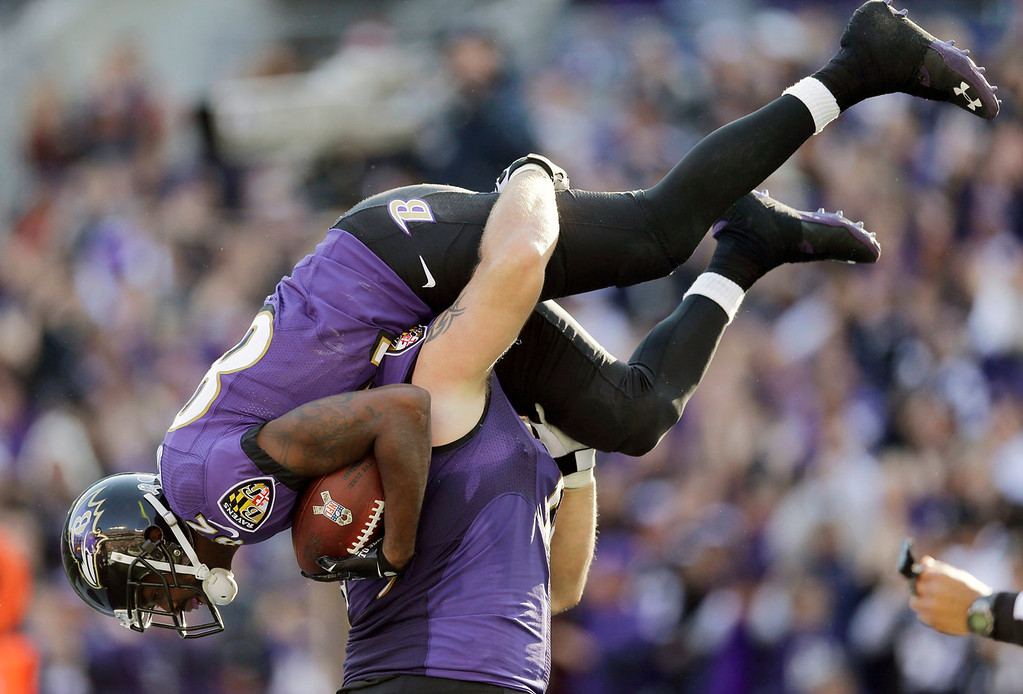. Baltimore Ravens guard Marshal Yanda picks up wide receiver Torrey Smith after Smith pulls in a touchdown pass during the first half of a NFL football game against the Cincinnati Bengals in Baltimore, Sunday, Nov. 10, 2013. (AP Photo/Patrick Semansky)