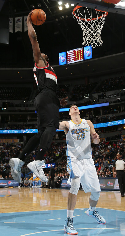 . Portland Trail Blazers guard Wesley Matthews, left, flies over Denver Nuggets center Timofey Mozgov, of Russia, to dunk the ball for a basket in the first quarter of an NBA basketball game in Denver, Tuesday, Feb. 25, 2014. (AP Photo/David Zalubowski)