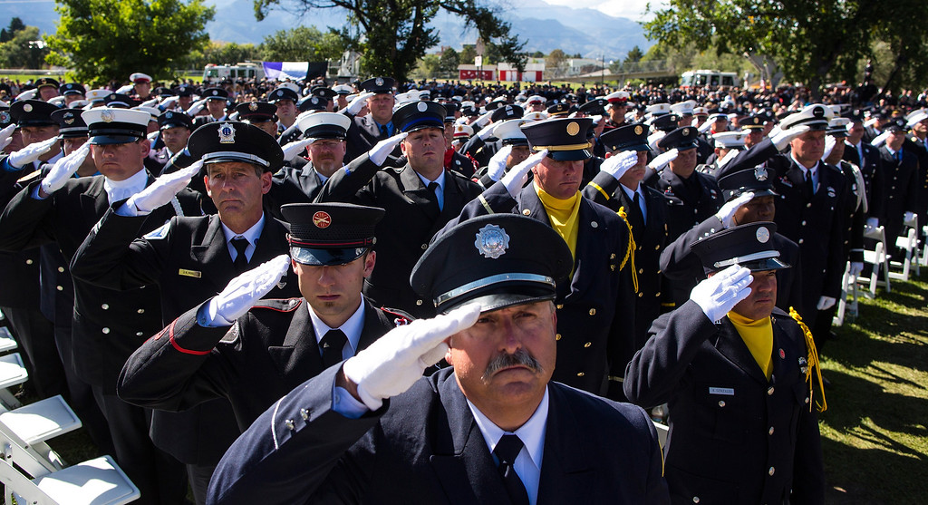 . Members of the IAFF Honor Guard stand at attention while the colors are retired during the annual IAFF Fallen Fire Fighter Memorial at Memorial Park in Colorado Springs, Colorado on Saturday, Sept. 21, 2013.(AP Photo/The Gazette, Kent Nishimura)