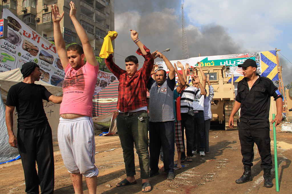 . Aug. 14, 2013: Egyptian security forces detain protesters as they clear a sit-in by supporters of ousted Islamist President Mohammed Morsi in the eastern Nasr City district of Cairo, Wednesday, Aug. 14, 2013. Riot police backed by armored vehicles and bulldozers cleared two sprawling encampments of supporters of ousted President Mohammed Morsi, sparking clashes that killed at least 638 people. (AP Photo/Ahmed Gomaa)
