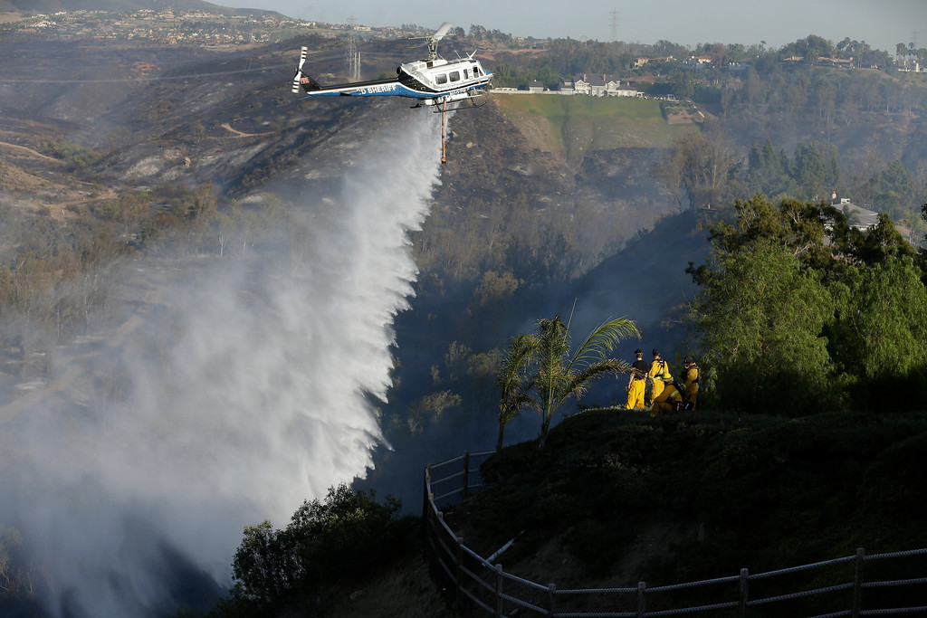 . Firefighters look on as a helicopter drops water on a wildfire in the Rancho Santa Fe neighborhood Tuesday, May 13, 2014, in San Diego. Wildfires pushed by gusty winds chewed through canyons parched by California\'s drought, prompting evacuation orders for more than 20,000 homes on the outskirts of San Diego and another 1,200 homes and businesses in Santa Barbara County 250 miles to the north. (AP Photo)