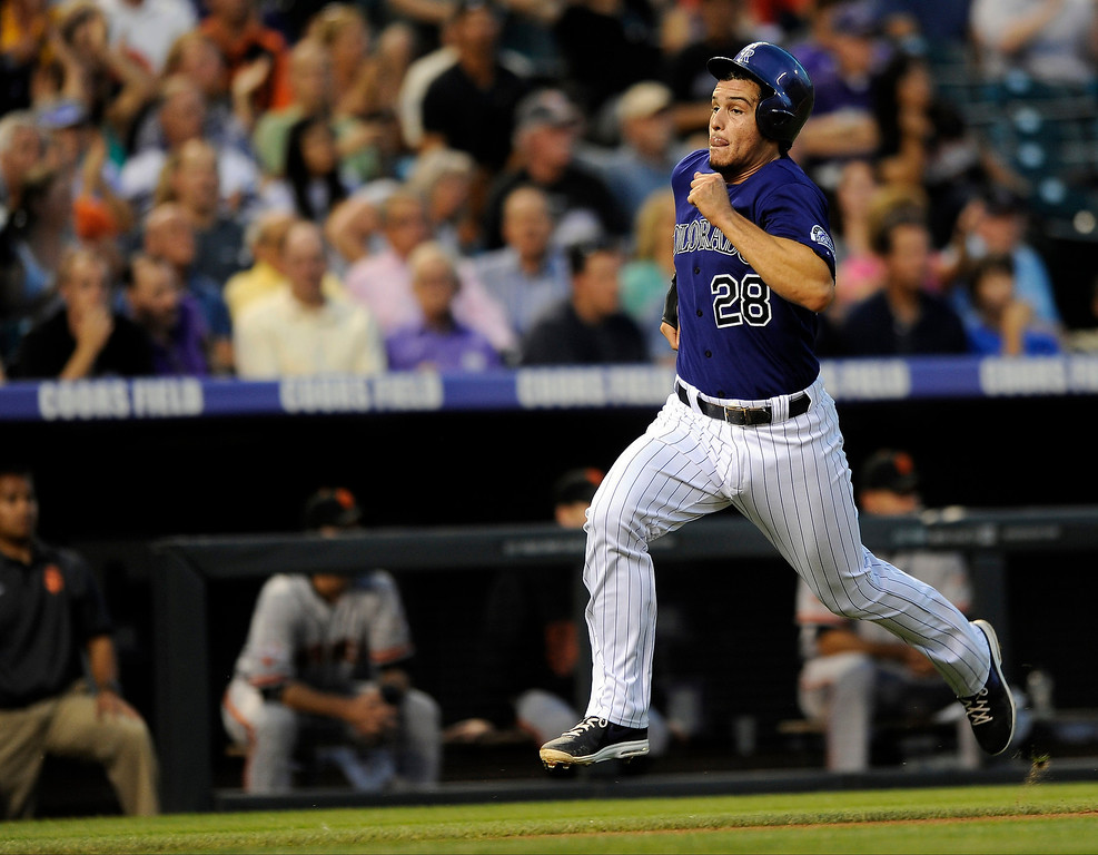 . Colorado Rockies\' Nolan Arenado runs home to beat the throw during the third inning of a baseball game on Tuesday, Aug. 27, 2013, in Denver. Arenado scored on a Charlie Blackmon RBI double. (AP Photo/Jack Dempsey)