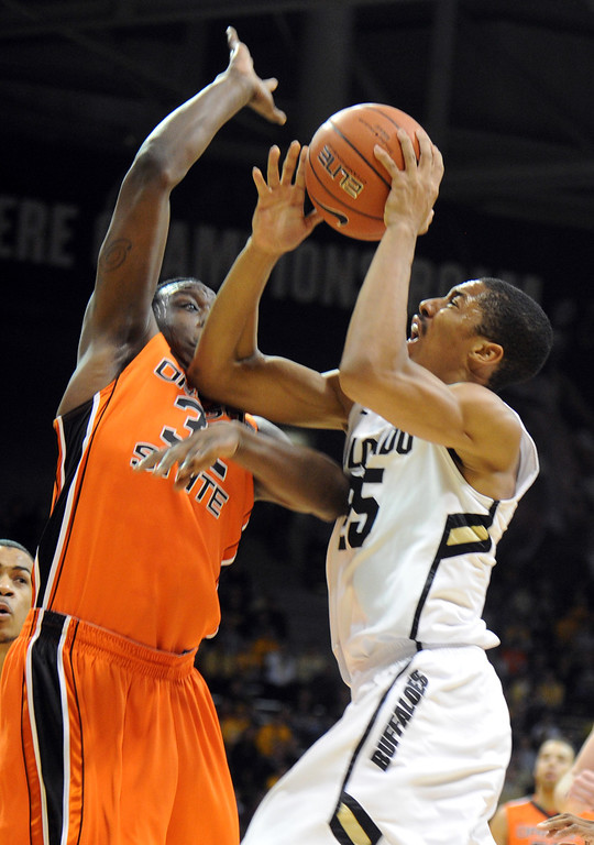 . Spencer Dinwiddie of CU drives on Jarmel Reid of OSU during the first half of the March 9, 2013 game in Boulder.    (Cliff Grassmick/Boulder Daily Camera)