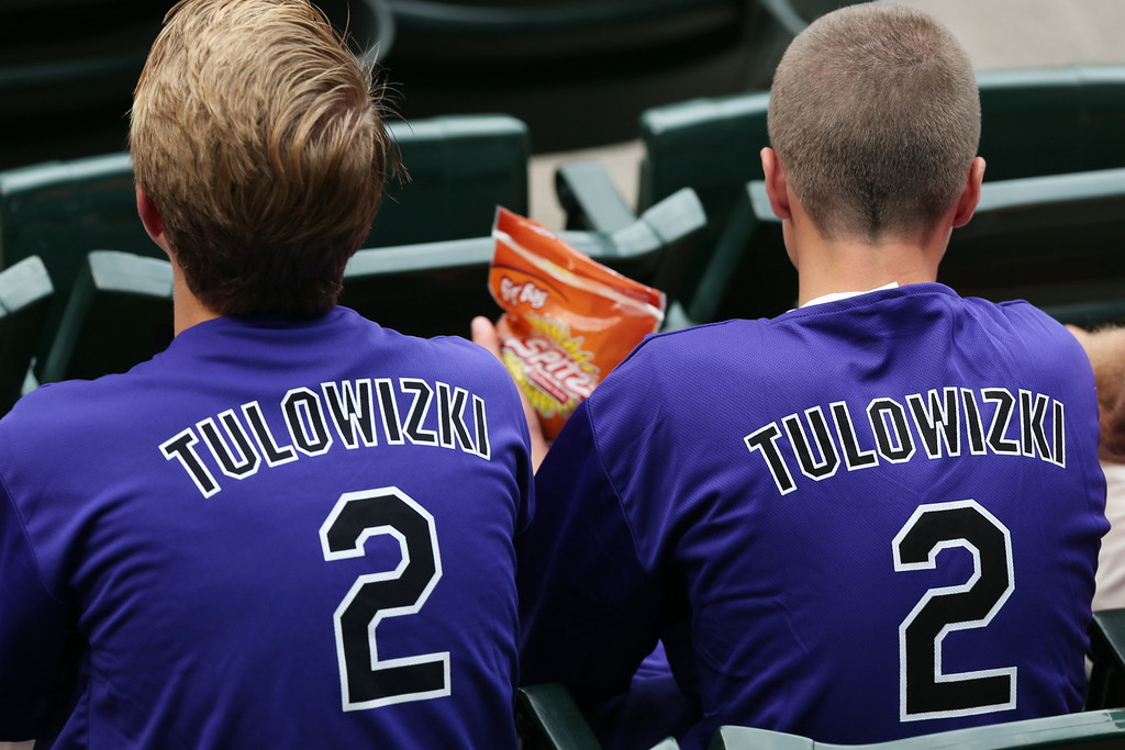 . Fans wear shirts emblazoned with the misspelled surname of Colorado Rockies All-Star shortstop Troy Tulowitzki that were given away to attendees as the Rockies hosted the Pittsburgh Pirates in a baseball game in Denver, Saturday, July 26, 2014. (AP Photo/David Zalubowski)