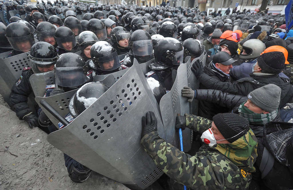 . Protesters clash with riot police during an anti-government protest in downtown Kiev, Ukraine, 22 January 2014. Two protesters have died during violent clashes with police in Kiev, Ukrainian opposition activists said 22 January 2014. The police have confirmed only one death so far. Forensic experts are examining the body of a dead man who was lying at a first aid location set up by the protesters, the Ukrainian Interior Ministry said.  EPA/ALEXEY FURMAN