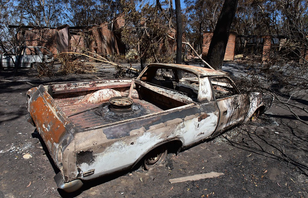 ". Burnt out cars sit in front of a destroyed house in Mount Victoria in the Blue Mountains on October 21, 2013, as volunteer fire brigades race to tame an enormous blaze with officials warning it could merge with others to create a ""mega-fire\"" if weather conditions worsen.   AFP PHOTO/William WEST/AFP/Getty Images"