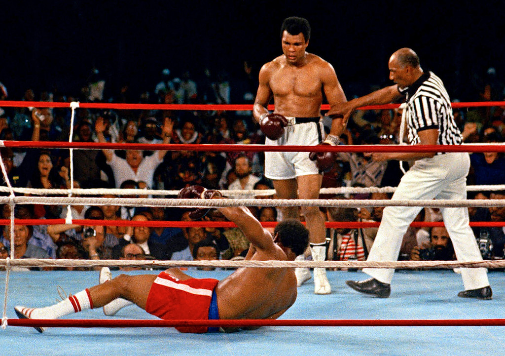 ". FILE - In this Oct. 30, 1974 file photo, referee Zack Clayton, right, steps in after challenger Muhammad Ali looks on after knocking down defending heavyweight champion George Foreman in the eighth round of their championship bout in Kinshasa, Zaire. Ali regained the world heavyweight crown by knockout in the eighth round of the fight dubbed ""Rumble in the Jungle.\"" (AP Photo/File)"