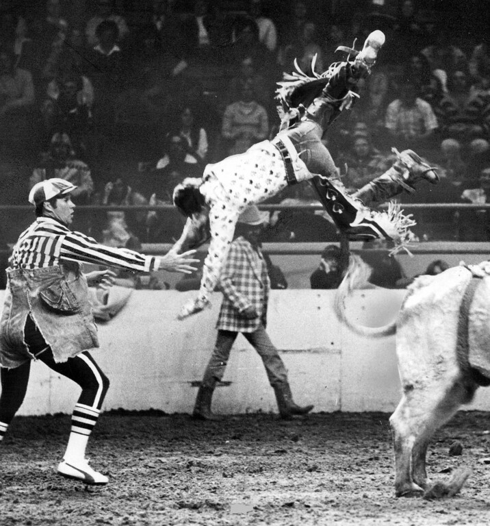 """. Lee Vogel, Stanton, Neb., is firmly aboard his mount, above, during senior boys bull-riding contest in the Little Britches. Rodeo. He bailed out, left, after riding for the full time period. Rodeo clown Bob Donaldson reaches out to break Vogel\'s fall. The night competition in the Denver Coliseum was part of EQUUS, the \""""Western World Fair\"""" at the National Western Stock Show complex. Some of the top \'Little Britches cowboys and cowgirls from throughout the nation are competing in the rodeo. 1977. Lyn Alweis, The Denver Post  Credit: Denver Post Photo"""