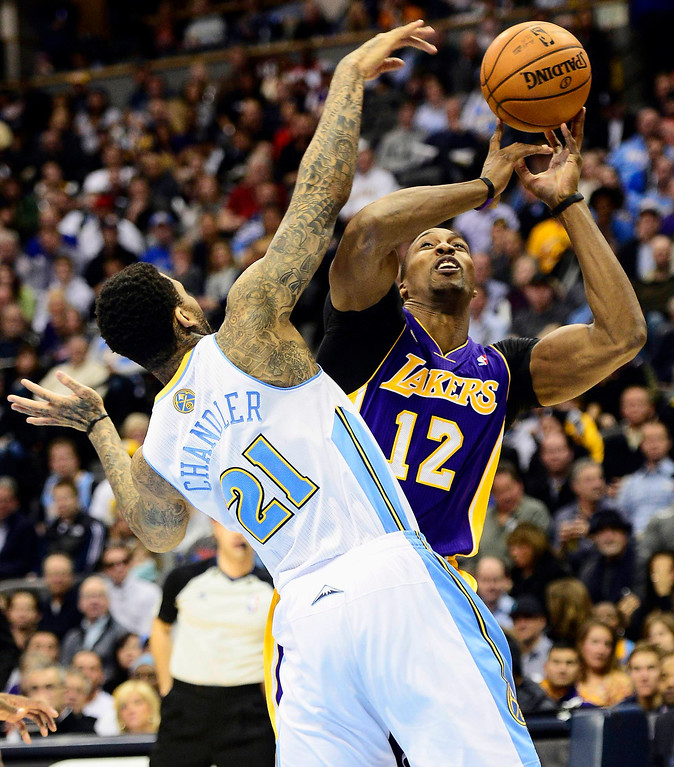 . Los Angeles Lakers\' Dwight Howard (R) looses control of the ball under pressure from Denver Nuggets\' Wilson Chandler during their NBA basketball game in Denver, Colorado February 25, 2013.   REUTERS/Mark Leffingwell