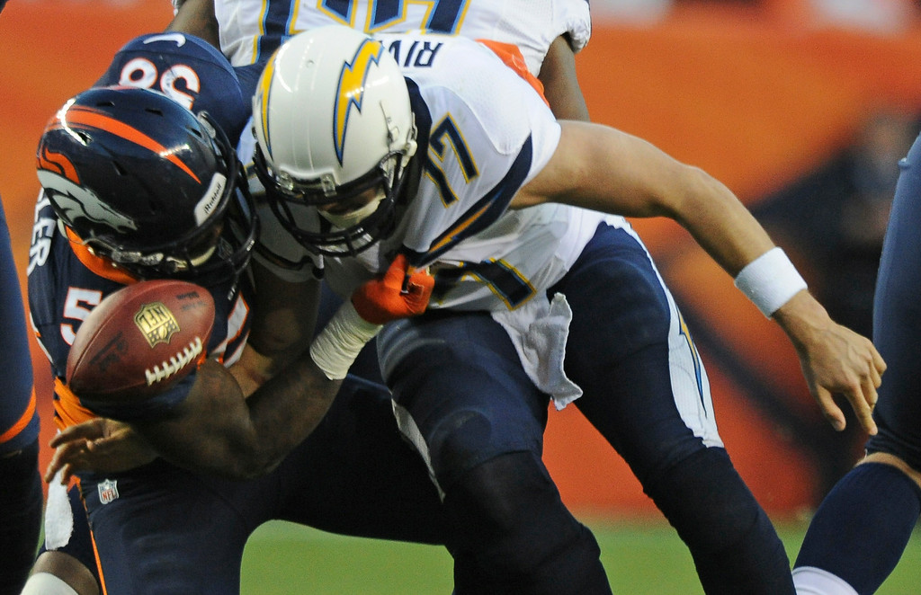 . Von Miller, left, knocks the ball out of Philip Rivers\' hands for a fumble that was recovered by the Broncos. (Tim Rasmussen, The Denver Post)