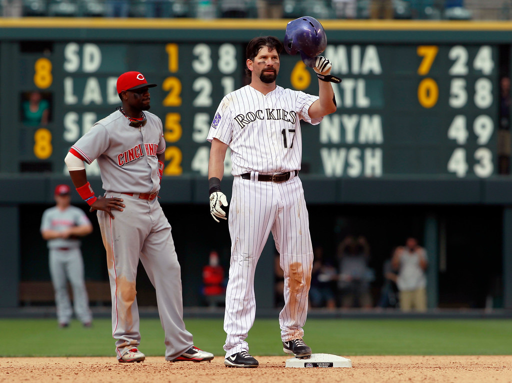 . Colorado Rockies\' Todd Helton, front, tips his helmet to the crowd as Cincinnati Reds second baseman Brandon Phillips looks on after Helton doubled in the seventh inning for his 2,500th career hit in the Rockies\' 7-3 victory in a baseball game in Denver on Sunday, Sept. 1, 2013. (AP Photo/David Zalubowski)