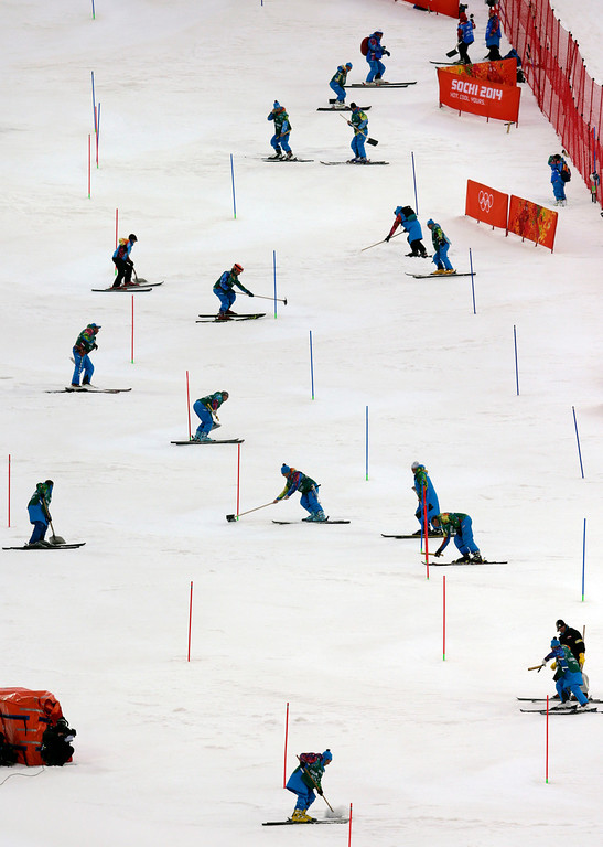 . Workers clean the course during the first run of the women\'s slalom at the Sochi 2014 Winter Olympics, Friday, Feb. 21, 2014, in Krasnaya Polyana, Russia. (AP Photo/Charles Krupa)