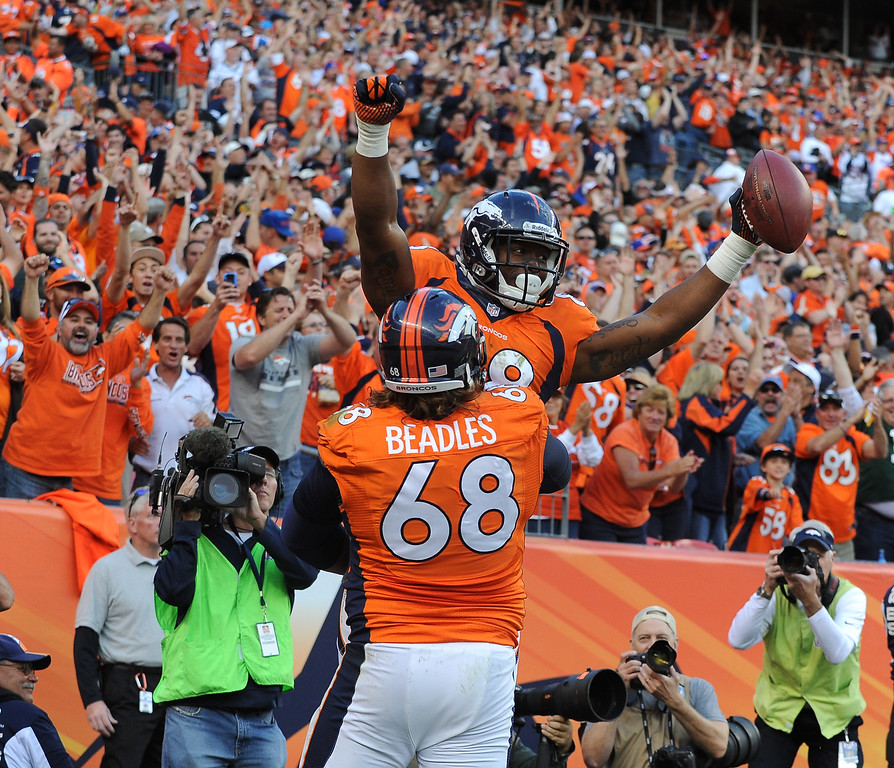 . Denver Broncos wide receiver Demaryius Thomas (88) is lifted by  guard Zane Beadles (68) after scoring a touchdown during the fourth quarter. The Denver Broncos vs. the Washington Redskins at Sports Authority Field at Mile High in Denver on October 27, 2013. (Photo by Tim Rasmussen/The Denver Post)