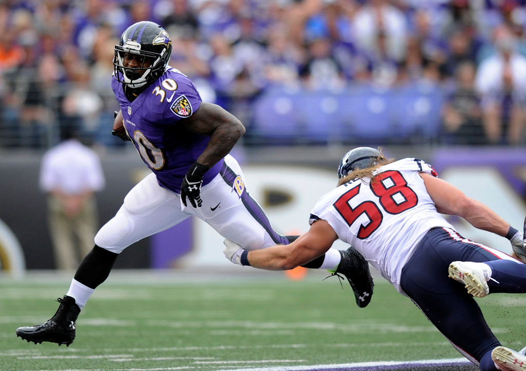 . Baltimore Ravens running back Bernard Pierce, left, rushes past Houston Texans outside linebacker Brooks Reed in the second half of an NFL football game Sunday, Sept. 22, 2013, in Baltimore. (AP Photo/Nick Wass)